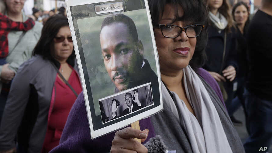 Val Scott holds up a photo of Martin Luther King Jr. during a march to mark the birthday of the slain civil rights leader in San Francisco, Jan. 15, 2018.