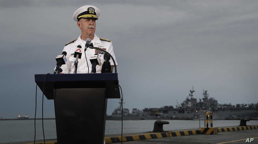 Commander of the U.S. Pacific Fleet, Scott Swift answers questions during a press conference with the USS John S. McCain and USS America docked in the background at Singapore's Changi naval base in Singapore, Aug. 22, 2017.