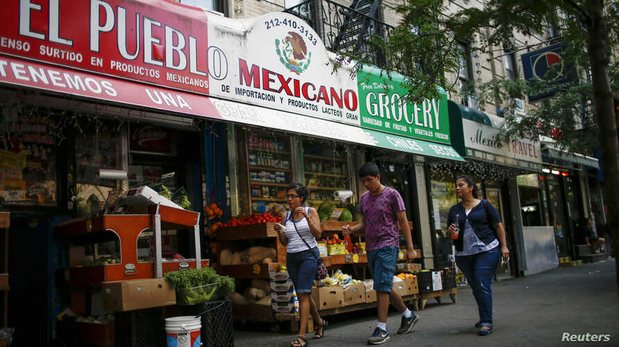 FILE - People pass by a Mexican grocery store in Harlem, New York, Aug. 10, 2014.