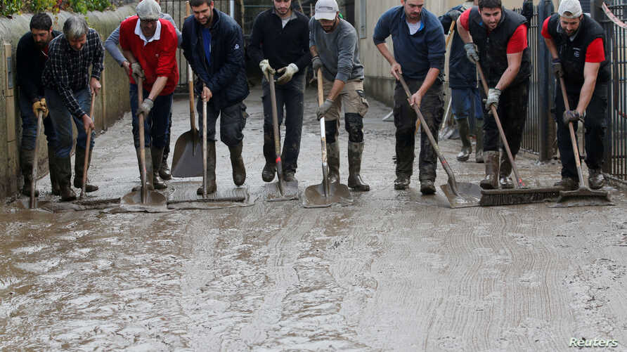 People use shovels and brooms to clean away mud as clean-up operations continue the day after some of the worst flash floods in a century turned rivers into raging torrents that engulfed homes and swept away cars hit the southwestern Aude district of