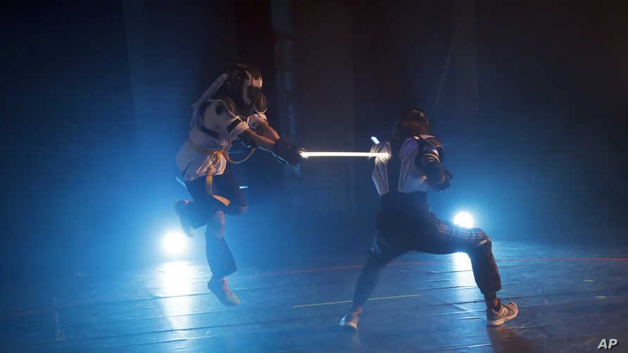 In this Feb. 10, 2019, photo, competitors battle during a national lightsaber tournament in Beaumont-sur-Oise, north of Paris.