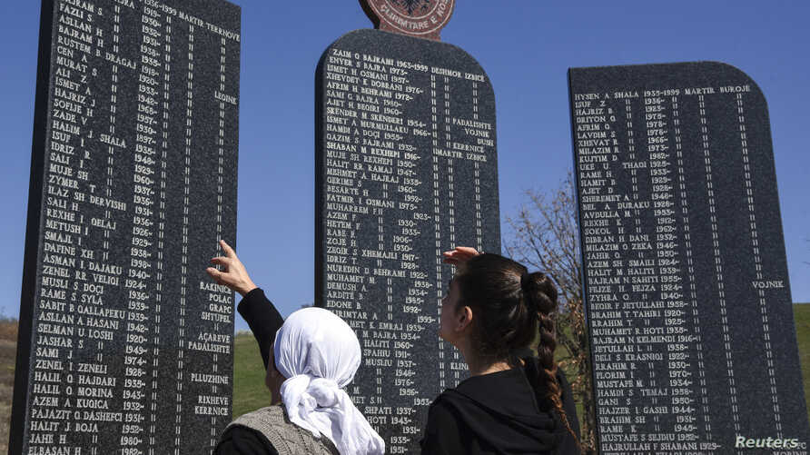 Kosovo Albanians read the names of the victims killed during the 1998-1999 Kosovo war, as part of a ceremony marking the 18th anniversary of the massacre in the village of Izbica on March 28, 2017.