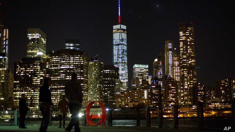 The One World Trade Center spire is lit blue, white and red after New York Gov. Andrew Cuomo announced the lighting in honor of dozens killed in the Paris attacks, Nov. 13, 2015.