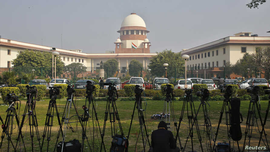 A television journalist sets his camera inside the premises of the Supreme Court in New Delhi. India's Supreme Court commuted death sentences on three men for involvement in the killing of former prime minister Rajiv Gandhi to life imprisonment becau