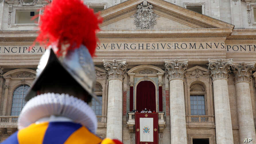 """A Swiss Guard stands as Pope Francis delivers his """"Urbi et Orbi"""" (to the city and the world) message from the balcony overlooking St. Peter's Square at the Vatican, Dec. 25, 2016."""