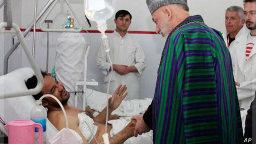 Afghan President Hamid Karzai talks with a victim wounded in a recent suicide bomb attack during an Ashura mourning procession, Kabul, Afghanistan, December 7, 2011.