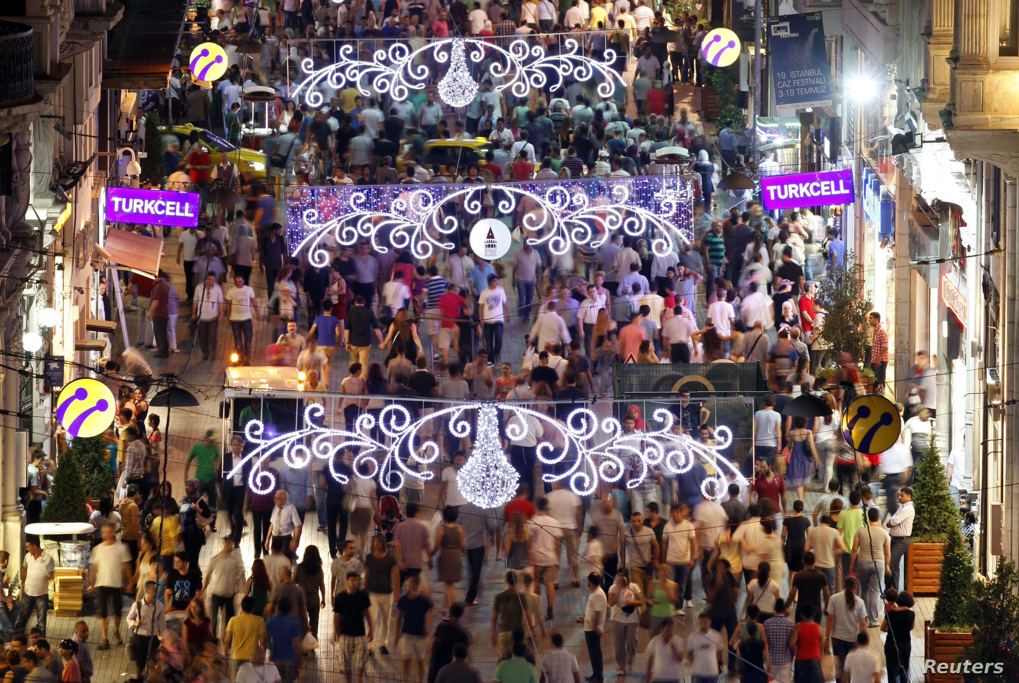 People walk along a main shopping street of Istiklal in Istanbul, Turkey, July 11, 2012.