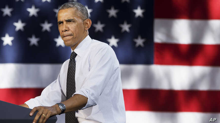 President Barack Obama pauses while speaking about the economy, July 9, 2014, at Cheesman Park in Denver.