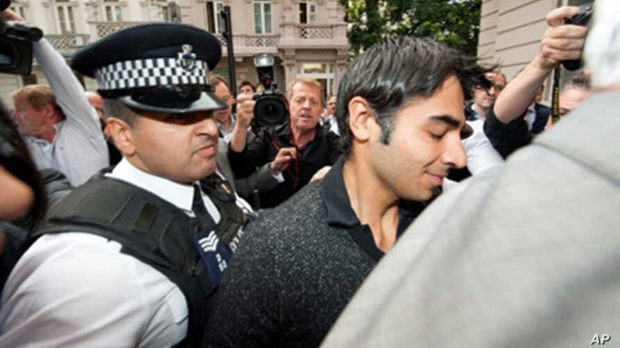 Pakistani cricketer Salman Butt (R) is escorted by a policeman through a scrum of media outside the Pakistan High Commission in London, 2 Sept. 2010.