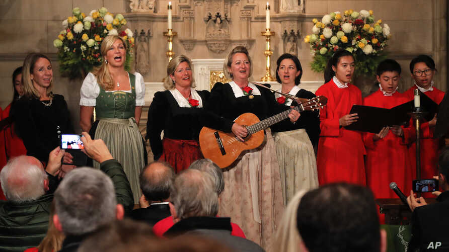 """The Kroell Family Singers, center, sing """"Silent Night"""" with the Choir of Trinity Wall Street and Trinity Youth Chorus during a celebration of the anniversary of the song at Trinity Church, Nov. 27, 2018, in New York."""
