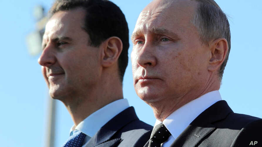 FILE - This Dec. 11, 2017 file photo, Russian President Vladimir Putin, right, and Syrian President Bashar Assad watch the troops marching at the Hemeimeem air base in Syria. (Sputnik, Kremlin Pool Photo via AP)