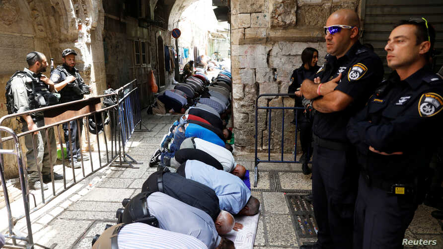 Palestinian men pray as Israeli forces secure the compound known to Muslims as Noble Sanctuary and to Jews as Temple Mount, in Jerusalem's Old City July 26, 2017.