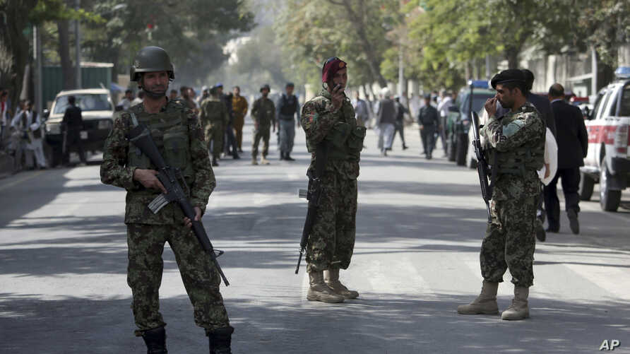 Afghanistan's National Army (ANA) soldiers stand guard at the site of an explosion on a road to the presidential palace, in Kabul, Afghanistan, Sept. 28, 2014.