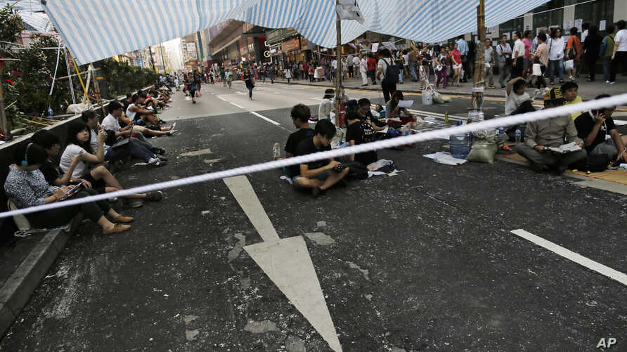 Protesters sit under a canopy at an intersection on a main road occupied by protesters in the Mong Kok area in Hong Kong, Tuesday, Oct. 7, 2014.