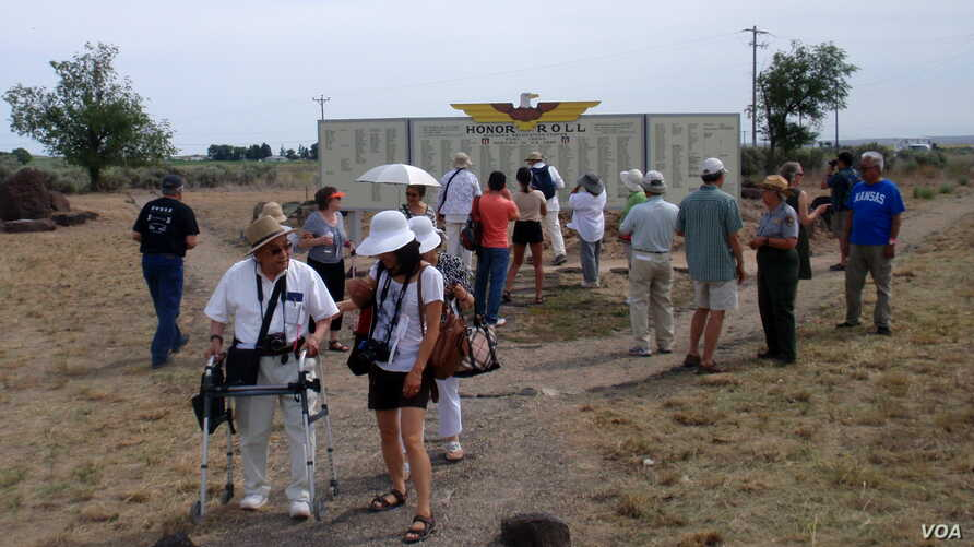 """Minidoka """"pilgrims"""" admire the re-created Honor Roll, which stood near the camp entrance and listed the names of internees who joined the U.S. armed forces during WWII, near Twin Falls, Idaho. (VOA / T. Banse)"""