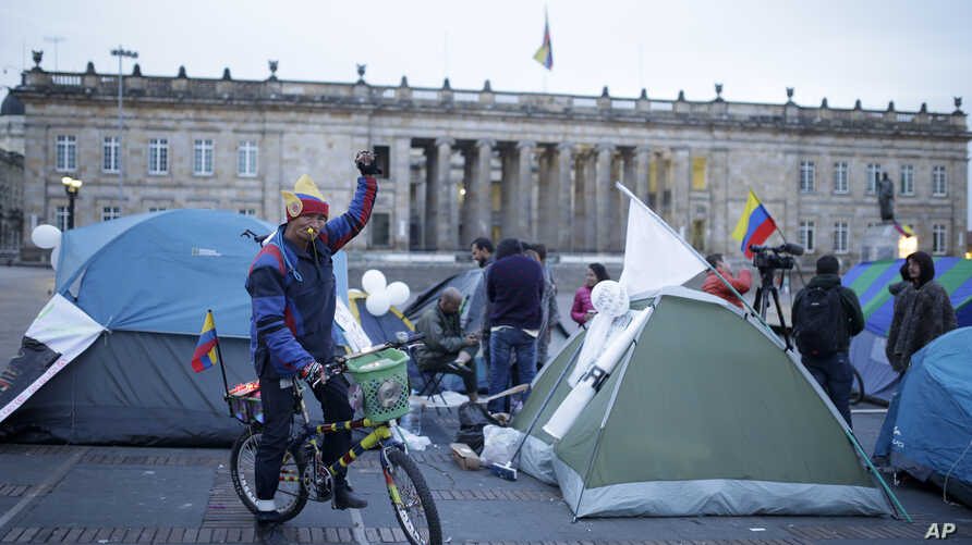 FILE - A cyclist raises his arm next to students camping to ask for peace at the main square in Bogota, Colombia, Oct. 7, 2016.