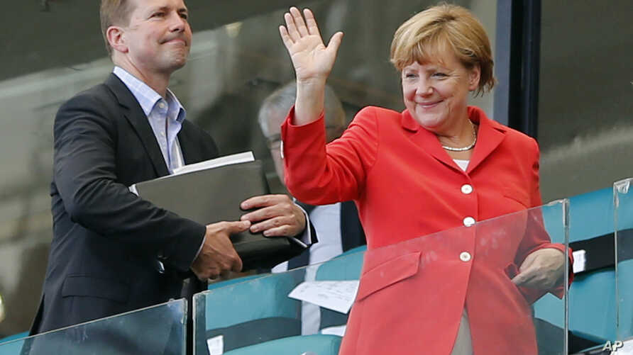 FILE - German President Angela Merkel waves after watching the group G World Cup soccer match between Germany and Portugal at the Arena Fonte Nova in Salvador, Brazil, June 16, 2014.