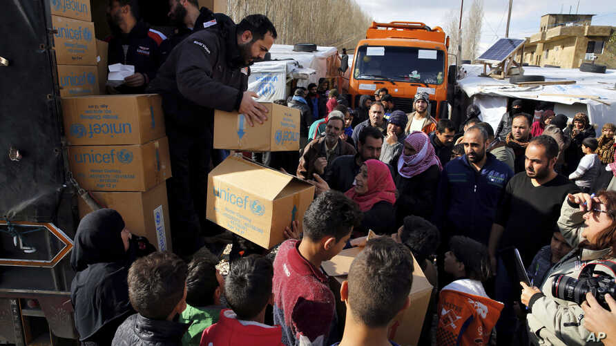 Workers distribute aid items from UNICEF to Syrian refugees at a camp in the town of Bar Elias, Bekaa Valley, Lebanon, Jan. 10, 2019.
