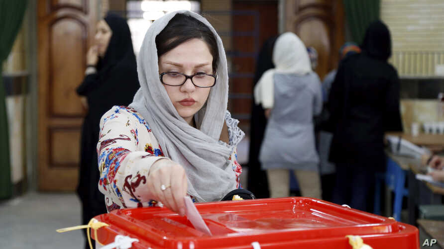 An Iranian woman casts her ballot for the parliamentary runoff elections in a polling station at the city of Qods about 12 miles (20 kilometers) west of Tehran, April 29, 2016.