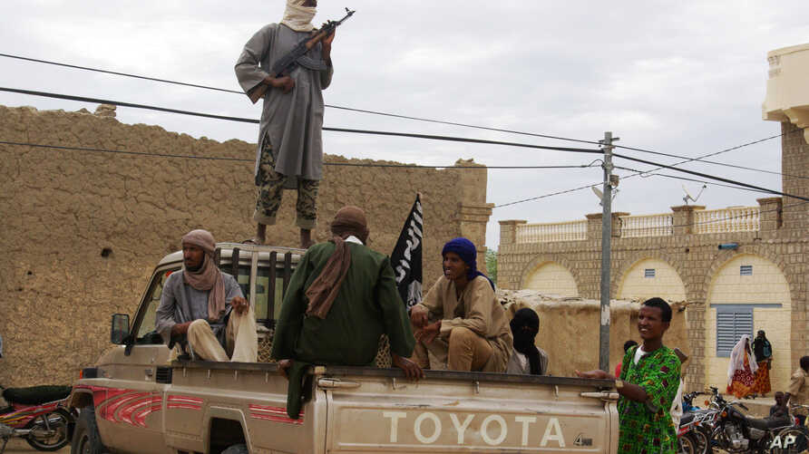 FILE - In this Aug. 31, 2012 file photo, fighters from Islamist group Ansar Dine stand guard in Timbuktu