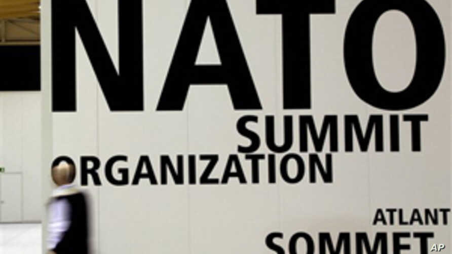 A man walks by a logo printed on a wall inside the NATO summit venue in Lisbon, Portugal on Thursday, Nov. 18, 2010. Heads of State of NATO member countries gather for a two day summit beginning on Friday, and will discuss such topics as Afghanistan