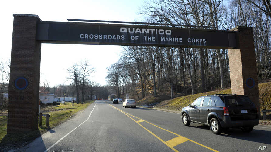 FILE - Cars pass under a sign at the entrance to the main gate at Quantico Marine Corps Base in Quantico, Va.  The Marine Corps is considering offering perks to entice older, more experienced Marines to re-enlist as it builds up its cyber operations.