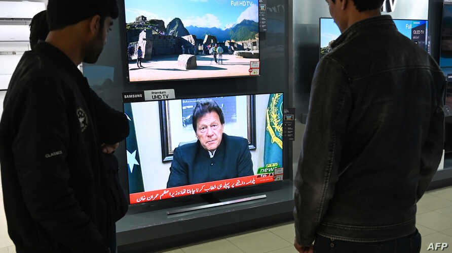 FILE - People watch Pakistani Prime Minister Imran Khan address the nation on TV following the Feb. 14 suicide bombing in Indian-administered Kashmir, in Islamabad, Feb. 19, 2019.