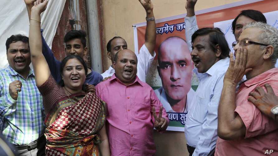 Friends of Indian naval officer Kulbhushan Jadhav celebrate the International Court of Justice order on Jadhav as they gather near a portrait of him in Mumbai, India, Thursday, May 18, 2017. The U.N. court on Thursday ordered Pakistan not to execute