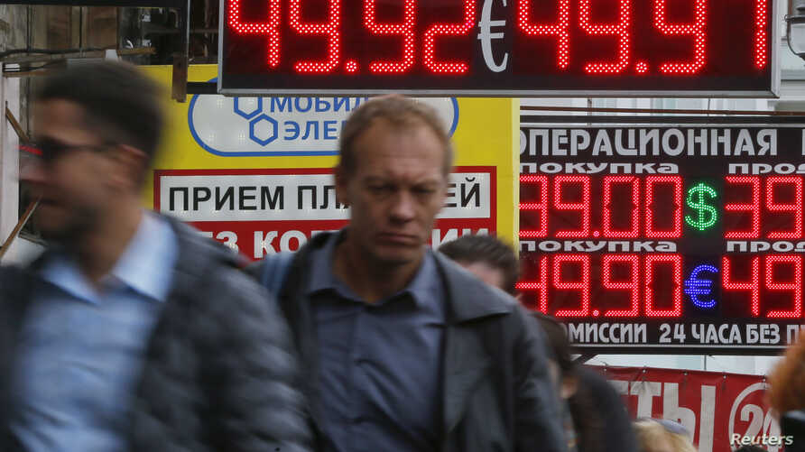 People walk along a street past a display showing currency exchange rates in Moscow Sept. 29, 2014.