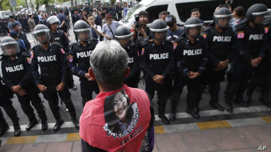 FILE - A Thai pro-democracy protester wears a scarf with a portrait of former Prime Minister Yingluck Shinawatra during a gathering to mark the fourth anniversary of the military takeover of government in Bangkok, Thailand, May 22, 2018.