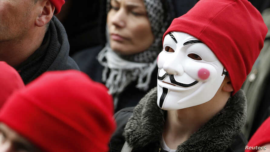 FILE - A protester wears a Guy Fawkes mask during a demonstration in Carhaix, western France, Nov. 30, 2013.