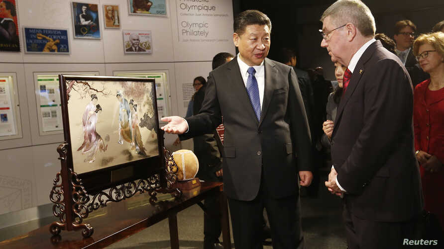 Chinese President Xi Jinping describes a gift showing a game of cuju to International Olympic Committee President Thomas Bach after a visit to the Olympic Museum in Lausanne, Switzerland, Jan. 18, 2017.