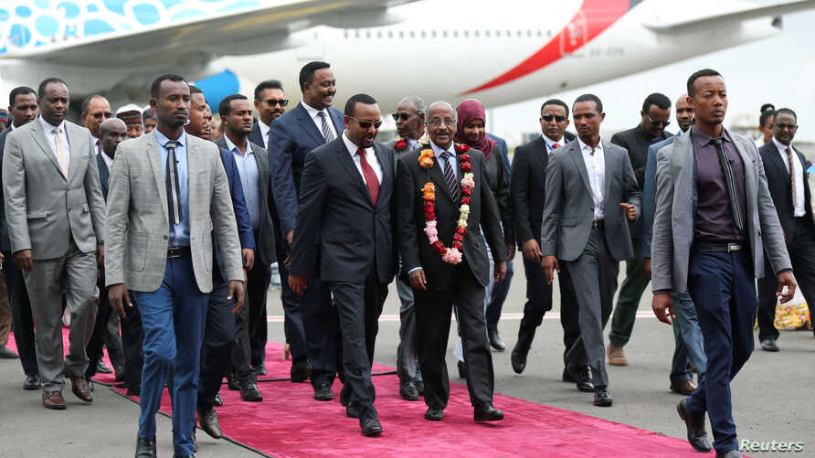Ethiopia's Prime Minister Abiy Ahmed welcomes Eritrean Foreign Minister Osman Saleh and his delegation at the Bole International Airport in Addis Ababa, Ethiopia, June 26, 2018.