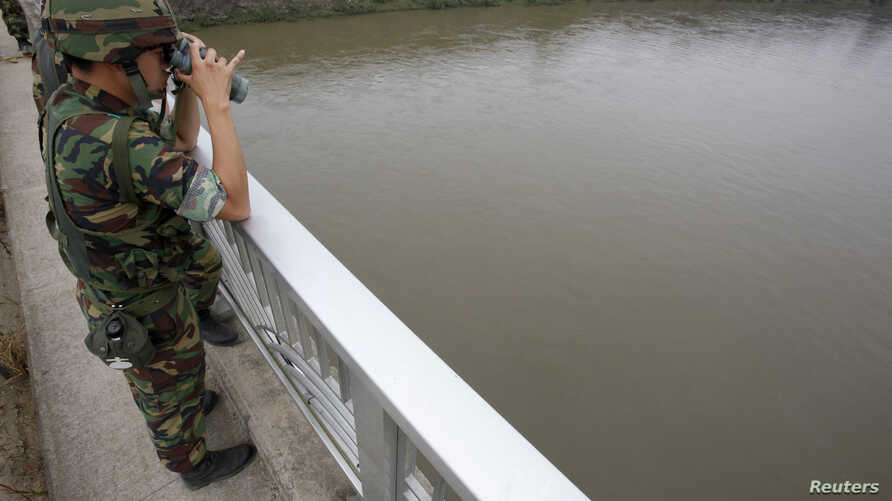 FILE - A South Korean army soldier standing on a bridge searches for missing people swept away by sudden rising water in the Imjin River near the demilitarized zone separating the two Koreas.