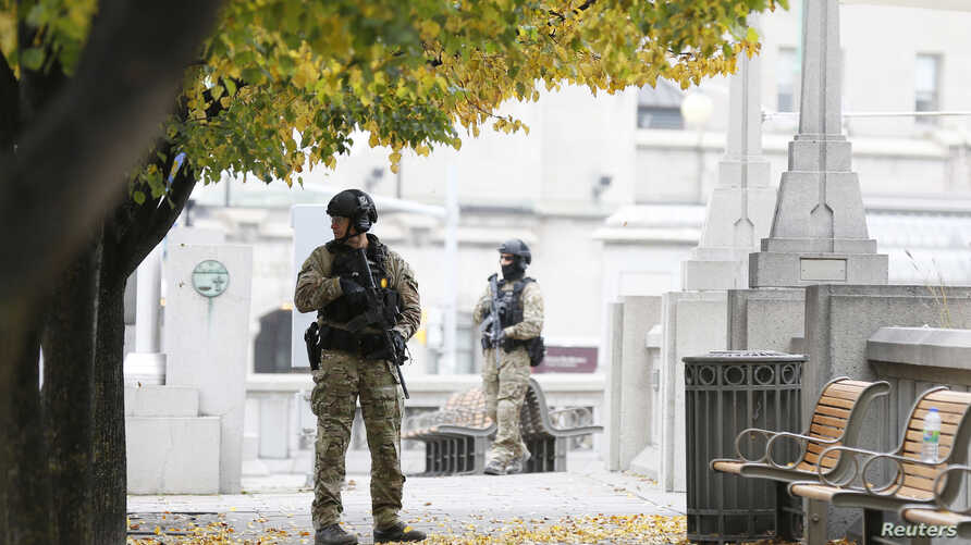 Police officers stand guard near the National War Memorial in downtown Ottawa October 23, 2014. A gunman attacked Canada's parliament on Wednesday, with gunfire erupting near a room where Prime Minister Stephen Harper was speaking, and a soldier was