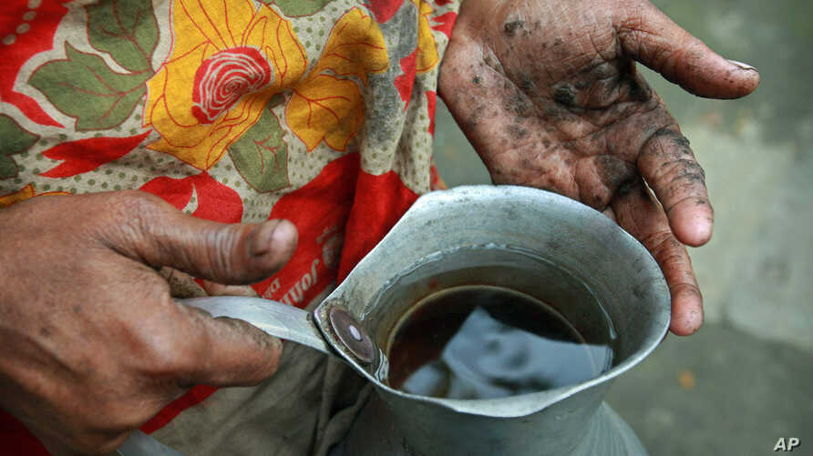 FILE - Hanufa Bibi, 45, holds a can full of contaminated well water, at her village in Chandipur, about 120 kilometers (75 miles) east of Dhaka, Bangladesh, Feb. 22, 2010.