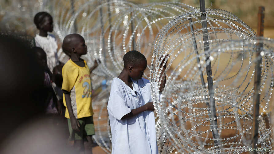 Internally displaced boys stand next to barbed wire inside a United Nations Missions in Sudan (UNMIS) compound in Juba December 19, 2013. South Sudanese government troops battled to regain control of a flashpoint town and sent forces to quell fightin