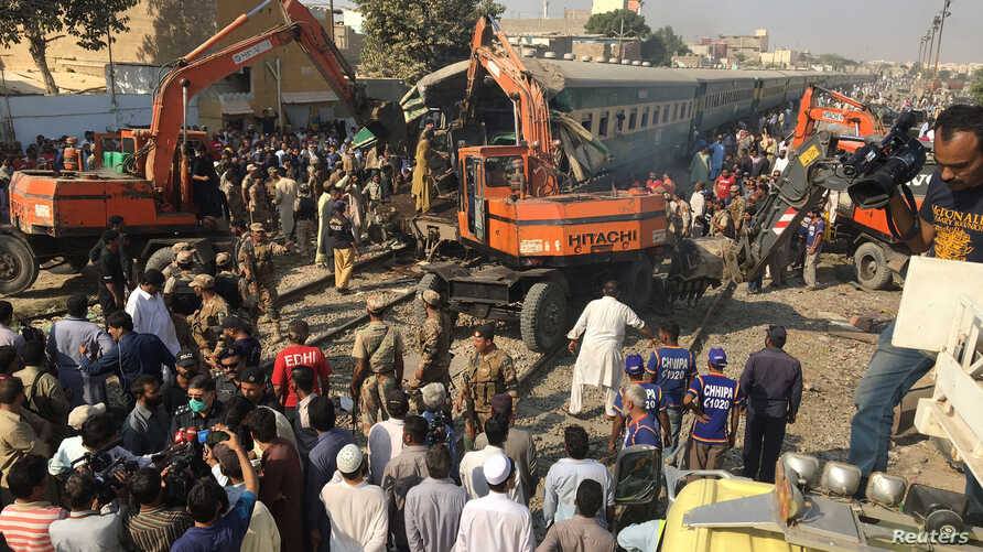 Rescuers workers use heavy machinery on the car of a train which crashed outside Karachi, Pakistan, Nov. 3, 2016.