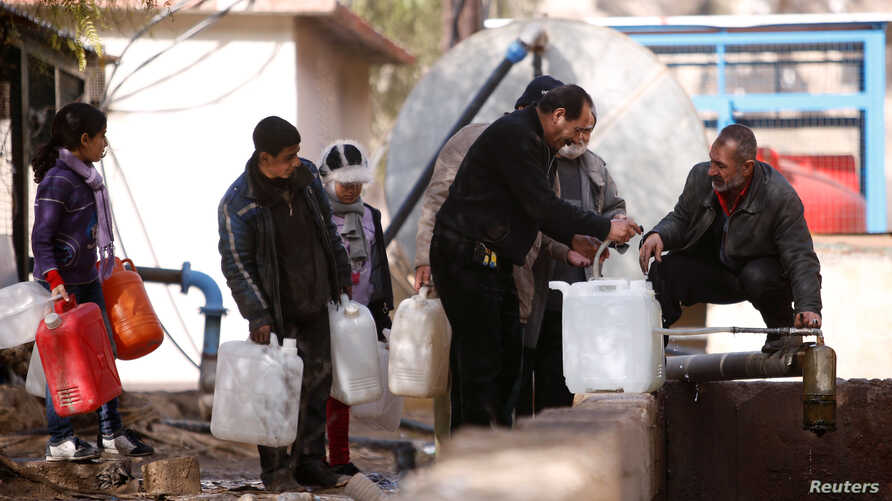 People queue as they fill containers with water in the government controlled al-Rabwah area, a suburb of Damascus, Jan. 10, 2017.
