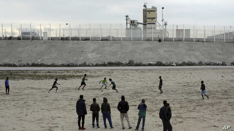 """Migrants play soccer in a makeshift camp that has been dubbed """"Jungle"""" by its residents, in Calais, France, Oct. 12, 2016."""