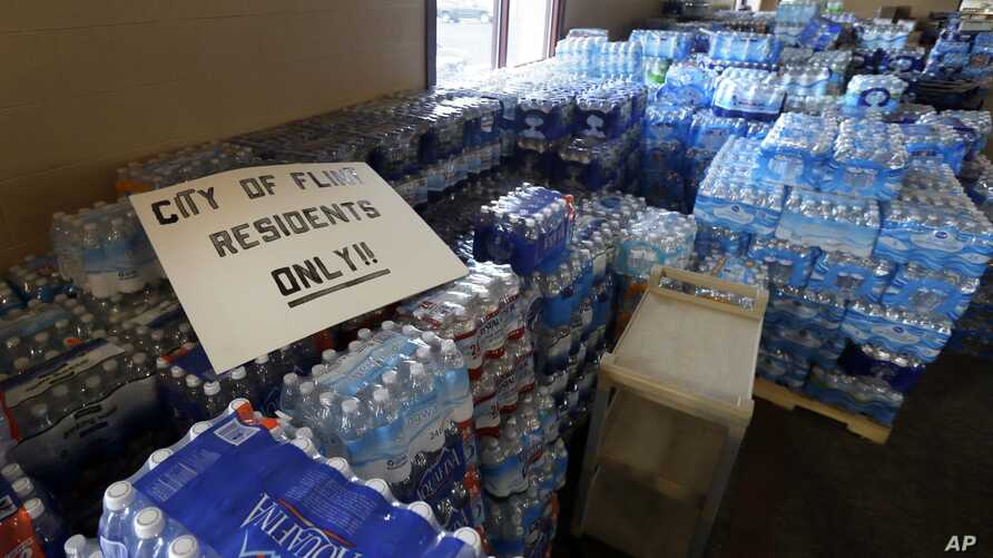 FILE - In this Friday, Feb. 5, 2016 file photo, hundreds of cases of bottled water are stored at a church in Flint, Mich.
