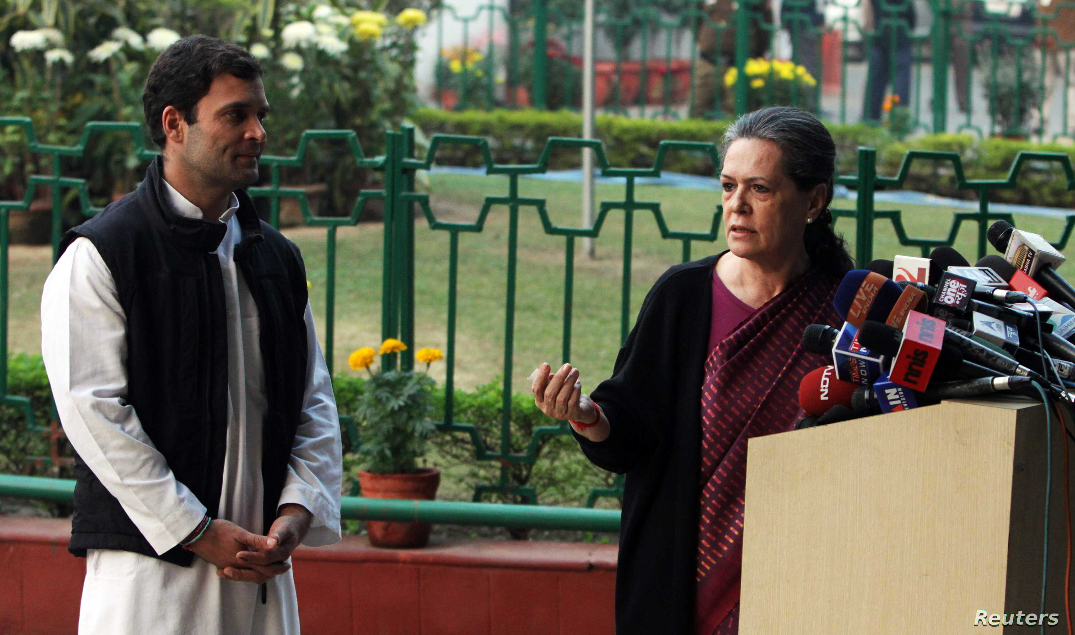 Chief of India's ruling Congress party Sonia Gandhi (R) speaks as her son, lawmaker Rahul Gandhi, watches during a news conference in New Delhi, Dec. 8, 2013.