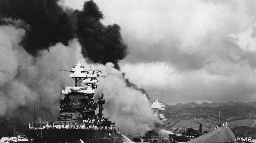 FILE - In this Dec. 7, 1941 file photo, part of the hull of the capsized USS Oklahoma is seen at right as the battleship USS West Virginia, center, begins to sink after suffering heavy damage, while the USS Maryland, left, is still afloat in Pearl Ha