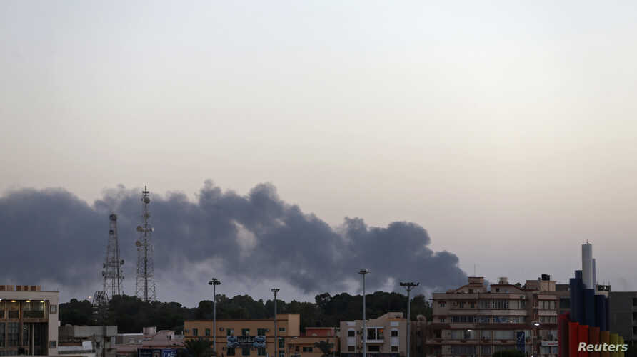 Black smoke rises from the vicinity of the University of Benghazi where clashes are taking place between pro-government forces and Islamist militias in Benghazi Oct. 18, 2014.