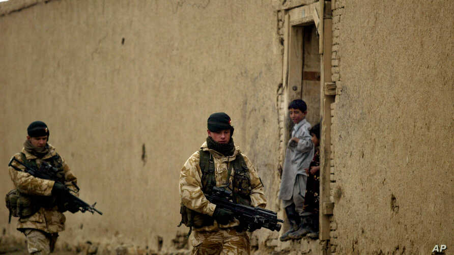 FILE - British soldiers from the Nato-led International Security Assistance Force patrol  as Afghan kids look on in the outskirts of Kabul, Afghanistan.
