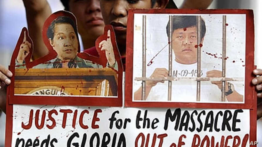An activist carries an anti-government placard showing a photo of President Gloria Macapagal Arroyo (L)  and a photo of Maguindanao Massacre suspect Mayor Andal Ampatuan (R), 01 Dec 2009