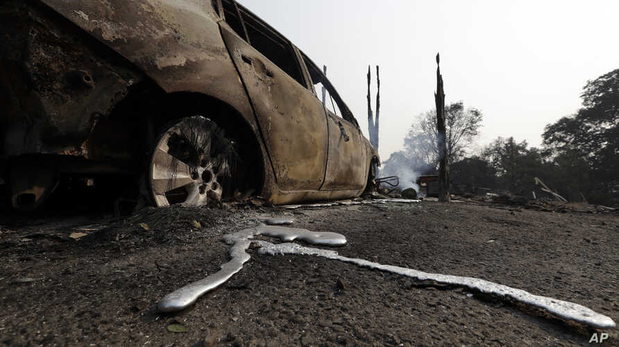 Melted metal is seen under a wildfire-damaged car, July 31, 2018, in Lakeport, California.