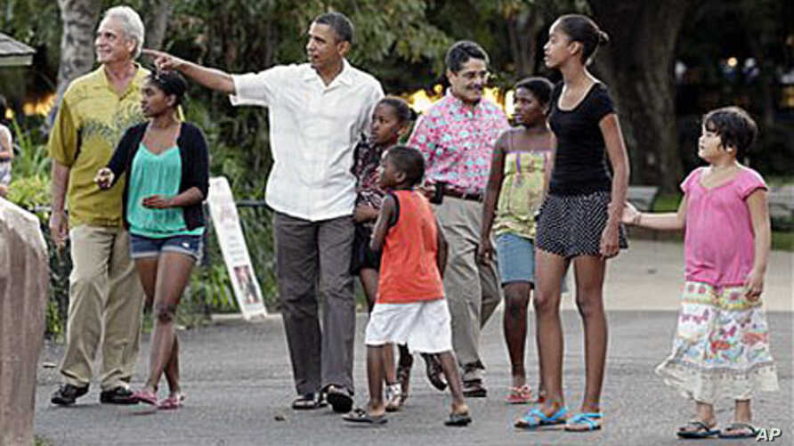 President Barack Obama walks with his daughters Sasha Obama, sixth from right, Malia Obama, second from right, and other family and friends through Honolulu Zoo, 3  Jan. 2011.