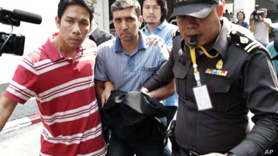 Thai police officers escort  Iranian suspect Mohammad Khazaei (C) at the Immigration Bureau in Bangkok February 16, 2012.
