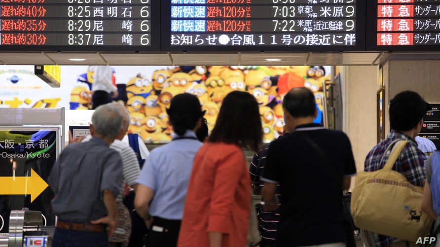 Passengers look at a noticeboard at Osaka station in Osaka, western Japan, as trains are delayed up to three hours due to rains from Typhoon Nangka, July 17, 2015.